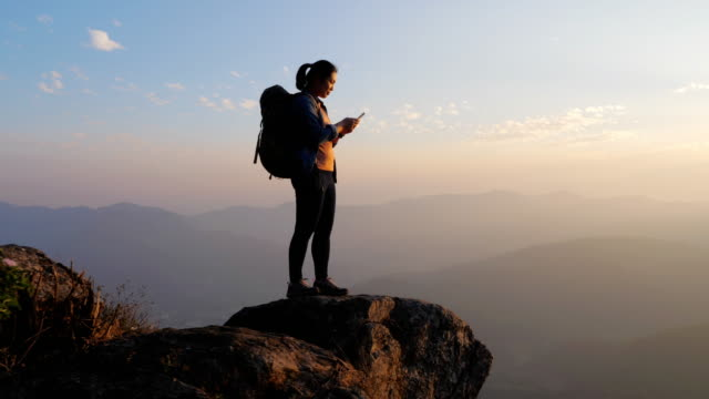 vidéos et rushes de femme de randonneur utilisant le téléphone portable sur le dessus de la montagne, communication - photophone