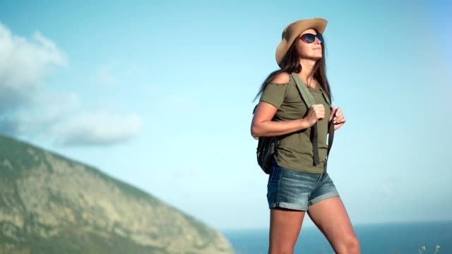 Hiker woman wearing sunglasses and hat enjoying trekking amazing landscape with sea and mountains