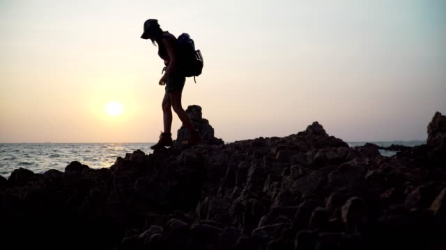 Hikers Asian women travel to explore the rock by the sea. Footage B roll of Hikers Asian women travel to explore the rock by the sea. Outdoors Hiking Silhouette. Climbing, Sea, Hiking Concept. Freedom and belief a success. Hands raised for worship. b roll stock videos & royalty-free footage