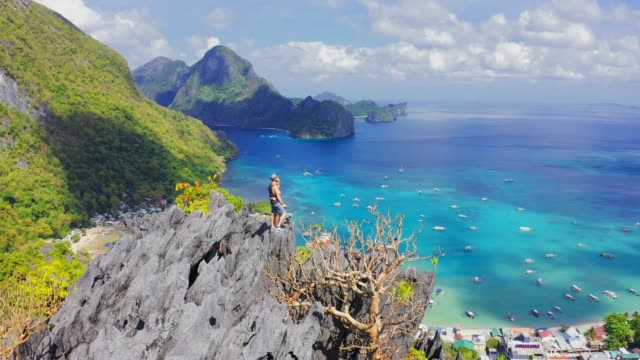 Hikers couple standing on top of a mountain and enjoying blue lagoon bay view in El Nido, Palawan, Philippines. 15 Jule 2019 - El Nido, Palawan, Philippines. Aerial view 4K