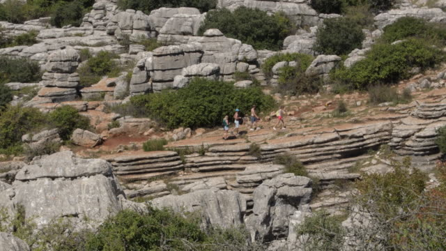 Hikers hiking with karst rocks in the natural reserve of Torcal, Antequera