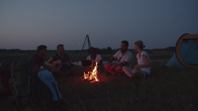 4K: Hikers Singing And Playing Guitar Around Campfire. video
