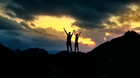 vidéos et rushes de hd: les randonneurs, debout sur un sommet avec soulevées mains - en haut
