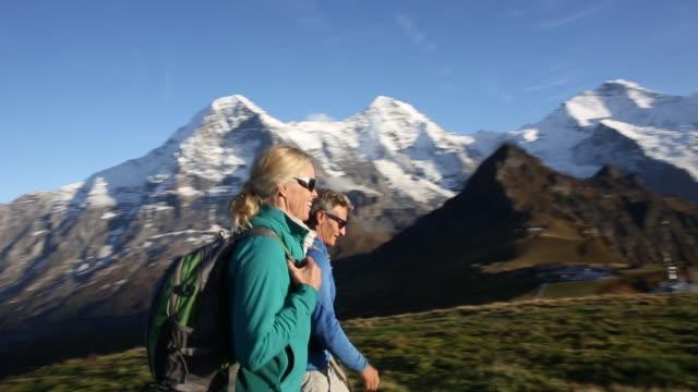 vídeos de stock e filmes b-roll de hikers traverse high alpine meadow at sunrise - 55 59 anos