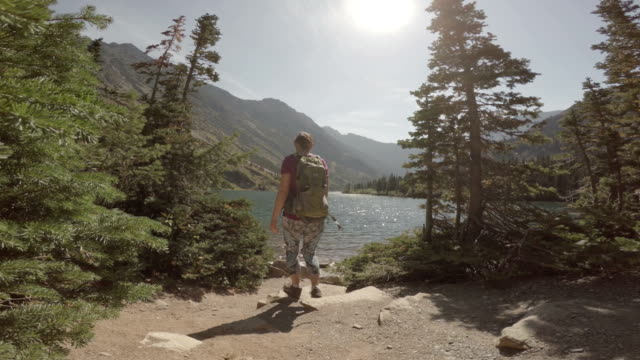 Hikers walk along mountain lake  pedal pushers stock videos & royalty-free footage