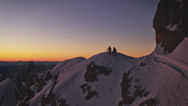 Hikers walking on snow covered ridge at sunrise