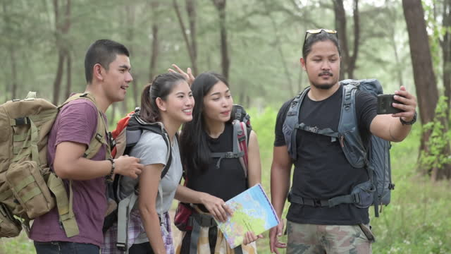 Hiking and camping concept. Asian hikers and men are using smartphones to make video live streaming to social media.