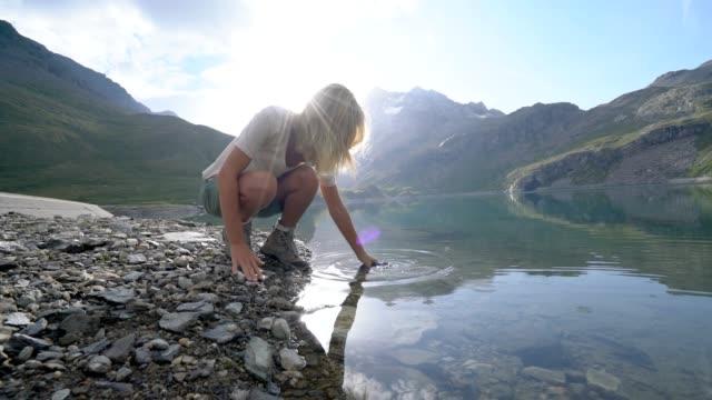 Blonde Mädchen Füllung Flasche wandern von Bergsee – Video