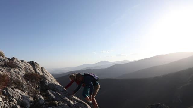 vandring par ascend rock ridge på sunrise - bergsrygg bildbanksvideor och videomaterial från bakom kulisserna