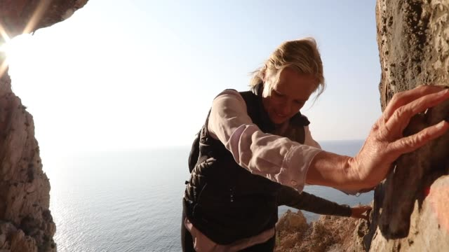 vídeos y material grabado en eventos de stock de pareja de senderismo ascender escarpado acantilado de roca en la cueva, al amanecer - escalada en rocas