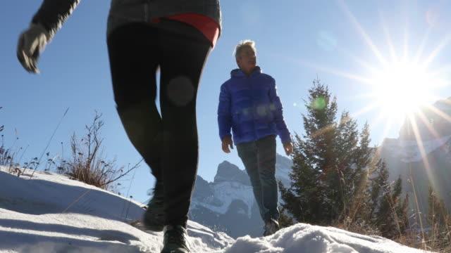 wandern paar folgt berg steig durch schnee, bei sonnenaufgang - freizeitaktivität im freien stock-videos und b-roll-filmmaterial