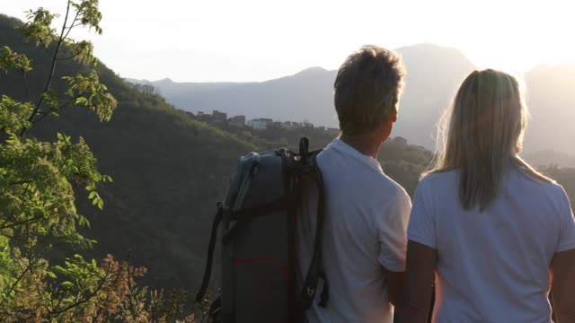 hiking couple pause above valley and mountains at sunrise - cinquantenne video stock e b–roll