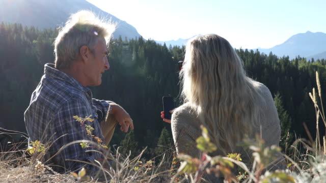 vandring par koppla av på gräsbevuxen toppmötet, använd smart telefon - klippiga bergen bildbanksvideor och videomaterial från bakom kulisserna