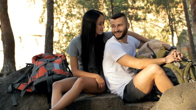 hiking couple talking at the forest - viaggiare zaino in spalla video stock e b–roll