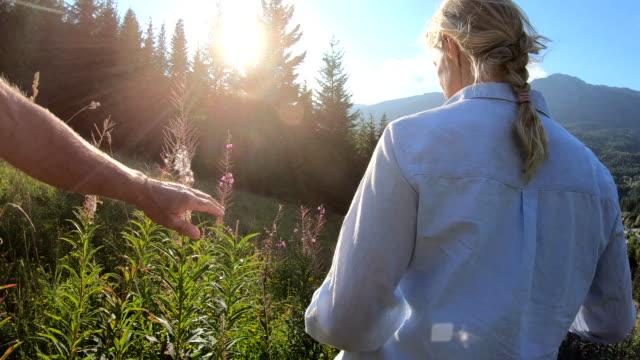 hiking couple traverse mountain slope at sunrise - cinquantenne video stock e b–roll