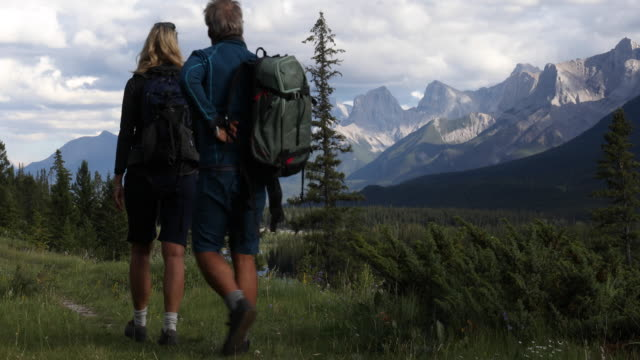 hiking couple walk along trail, past mountains - pantaloncini video stock e b–roll