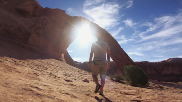 wandern auf dem colorado-plateau pov: corona arch in der nähe von moab - utah stock-videos und b-roll-filmmaterial