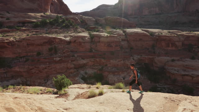 hiking in the colorado plateau: woman traveling alone - red rock video stock e b–roll