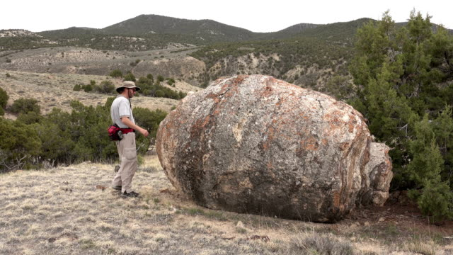 Hiking man explores ancient huge Ducey Stromatolite limestone fossil northwest Colorado video