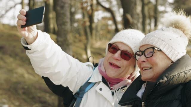 la coppia senior escursionistica si sta scattando selfie - abiti pesanti video stock e b–roll