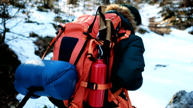 hiking the snow covered mountain 4k - турист с рюкзаком стоковые видео и кадры b-roll