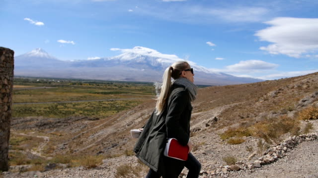 Hiking woman in sunglasses on travel excursion walking in mountain landscape at summer vacations video