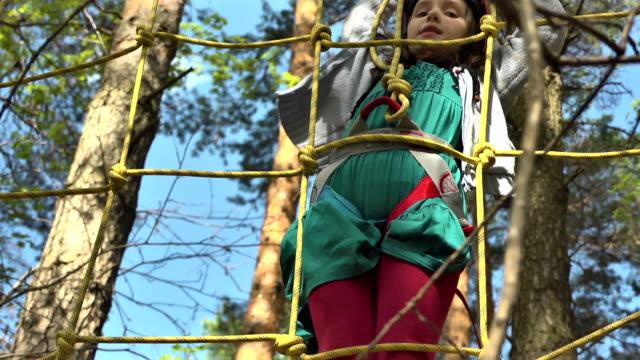 vídeos y material grabado en eventos de stock de сhild supera un obstáculo en el curso de cuerdas - cuerda
