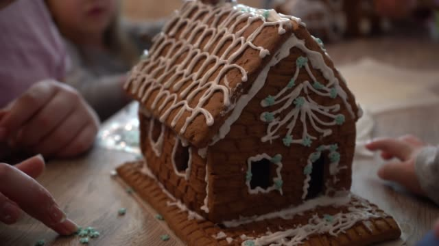 vídeos de stock e filmes b-roll de сhildren with parents make christmas gingerbread cookies. christmas gingerbread in the form of a house. children collect gingerbread before christmas. cream for gingerbread. - christmas cookies
