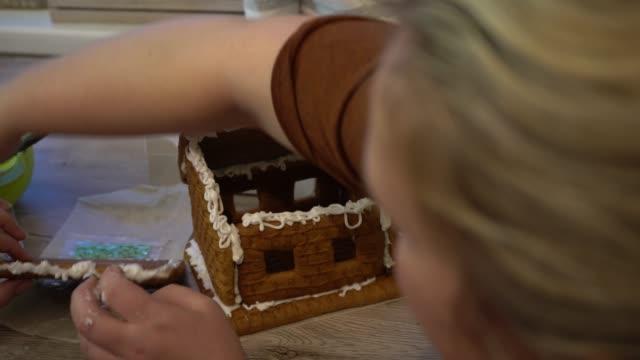 mit den eltern machen sie weihnachts-lebkuchenplätzchen. weihnachts-lebkuchen in form eines hauses. kinder sammeln vor weihnachten lebkuchen. creme für lebkuchen. - lebkuchenhaus stock-videos und b-roll-filmmaterial