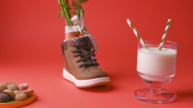 stockvideo's en b-roll-footage met hildrens schoen met wortelen voor het paard van de kerstman, melk, pepernoten en snoepjes op een heldere achtergrond. nederlandse feestdag sinterklaas. stop mo - pepernoten