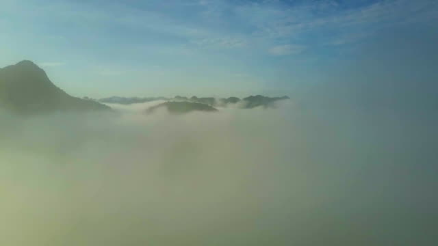 hill silhouettes above clouds and flycam dives into fog
