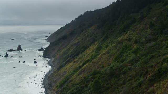 vídeos de stock e filmes b-roll de hillside descending to ocean on california lost coast - drone shot - montanha costeira