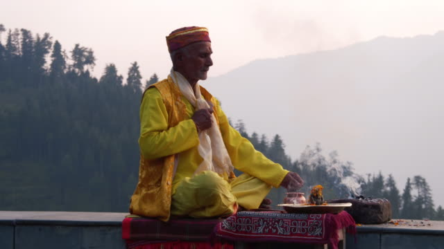 A Hindu Old Man In Yellow Offering Special Spiritual Prayer