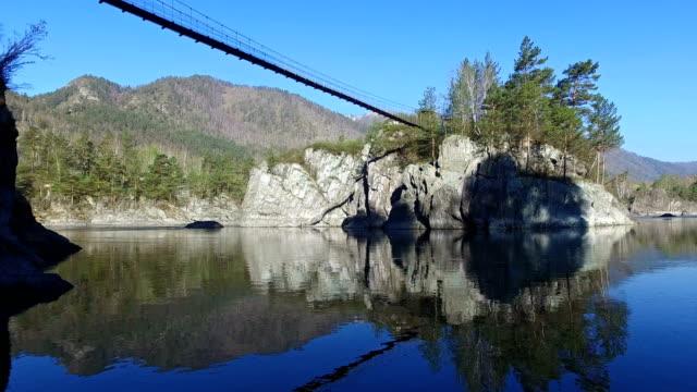 川 Chemal、アルタイ、ロシアのカトゥンにパトモス島の修道院に蝶番を付けられた橋 ビデオ