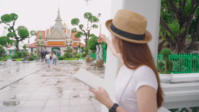 Hip Leinster girl standing scribbled something on a notebook while touring the Temple of Dawn. Popular locations in Thailand.