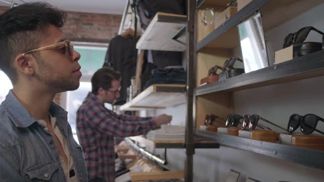 vídeos de stock, filmes e b-roll de ms. jovem hip experimenta óculos escuros e se olha no espelho em loja de roupas local de alta linha. - mercadoria