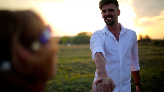 Hipp Couple Running In Field Holding Hands video