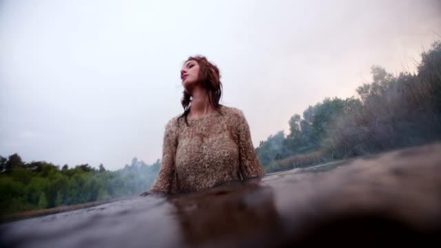 Hippie girl standing in a lake splashing water video