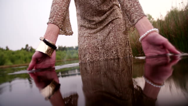 Hippie girl standing in a lake wearing a lace dress video