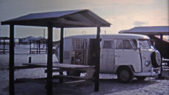 1971: hippie vw van parcheggiate spiaggia ragazze quinte. - hippy video stock e b–roll