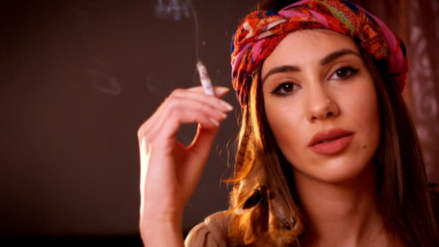 Hippie woman smoking cigarette Close-up video of beautiful woman looking at camera and smoking cigarette. hippie stock videos & royalty-free footage