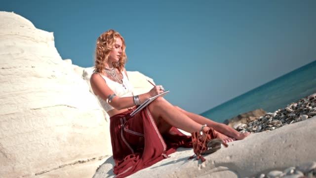 vídeos y material grabado en eventos de stock de mujer hippie con joyas dibujo en cuaderno de dibujo en la playa - moda playera