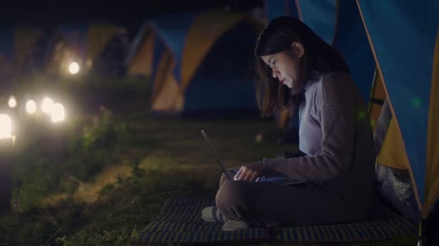 Hipster asian female camping an use laptop the nature