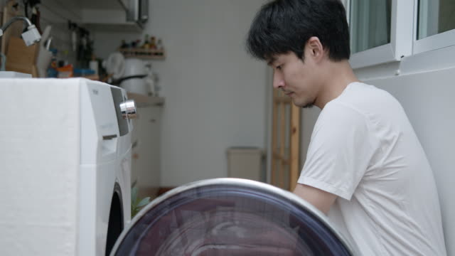 Hipster asian man doing laundry at home Man opens door of washing machine before loading laundry from basket and closing door. laundry basket stock videos & royalty-free footage