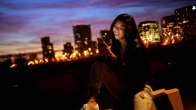 Hipster Asian teenage girl chatting online using smartphone in city Fashionable hipster Asian woman text messaging using smartphone against urban skyline with night lights filipino ethnicity stock videos & royalty-free footage