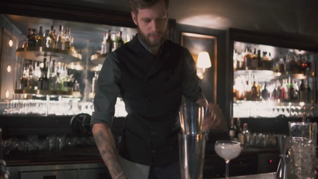 Hipster bartender mixologist combining ingredients and for preparing alcohol cocktails in beautiful modern bar video