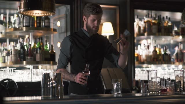 Hipster bartender mixologist combining ingredients and making a whiskey cocktail in beautiful modern bar. video