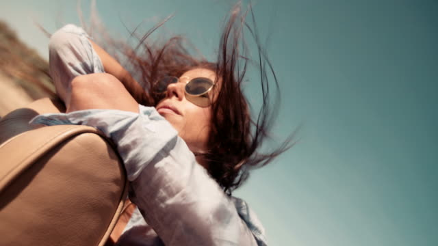 Hipster boho girl enjoys hair moved by the wind on  summer road trip video