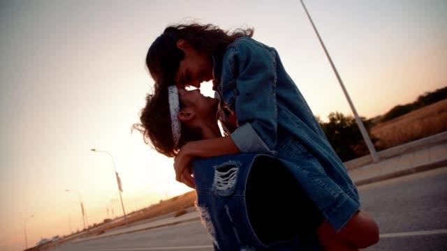 fidanzato hipster che raccoglie ragazza in city street al tramonto - love video stock e b–roll