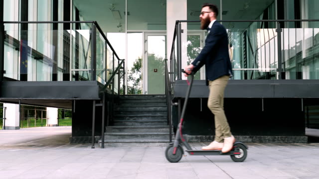 hipster businessman taking an electric scooter to work - monopattino elettrico video stock e b–roll